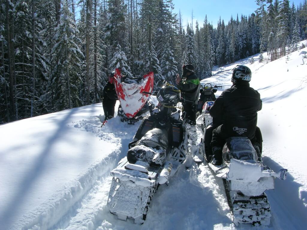 a few people doing some manning snowmobiling