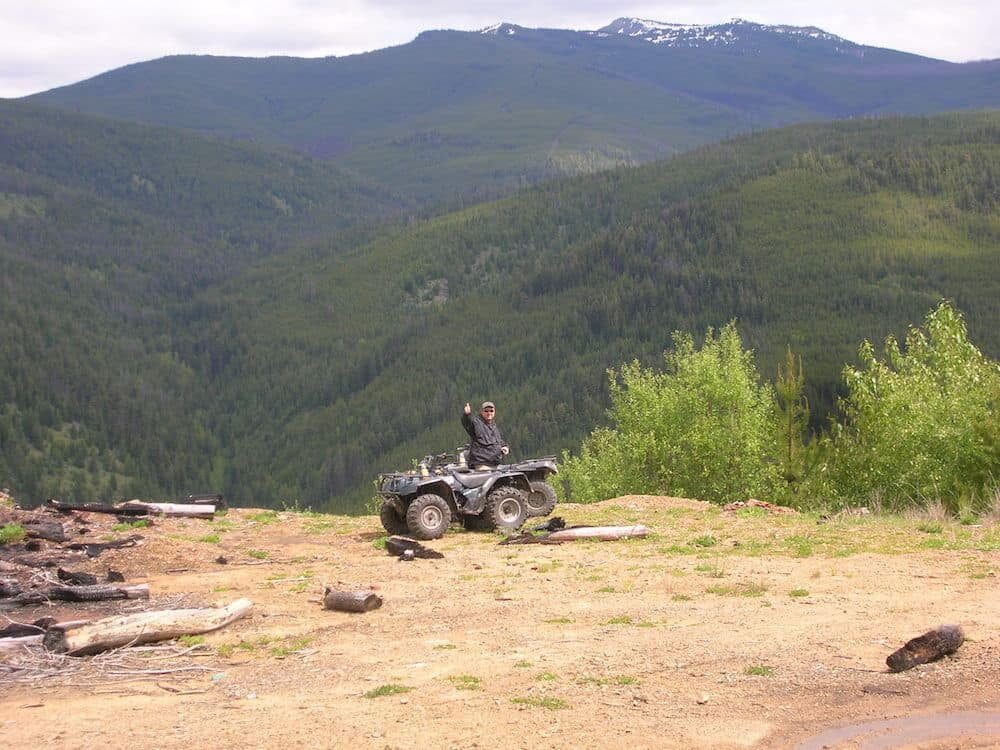 at the edge of a manning cliff a man is giving a thumbs up behind his atv