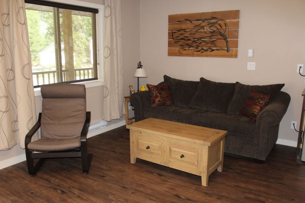 the living room with a couch and chair and table in our manning park accommodations